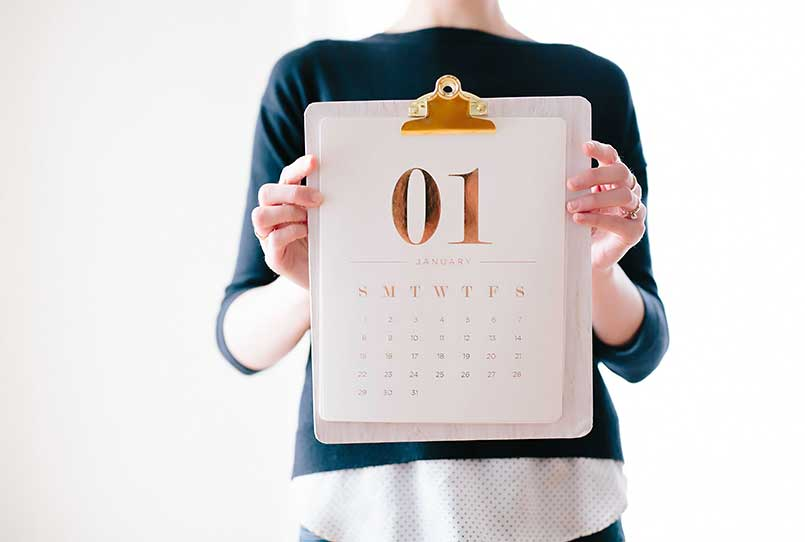 woman holding new year free printables calendar for 2021