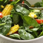 summer spinach salad recipe with honey lime dressing and fresh cut corn on the cob, in a white bowl