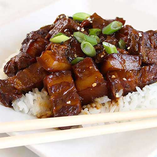 Chinese Braised Pork in Brown Sauce Recipe on a white plate with chopsticks