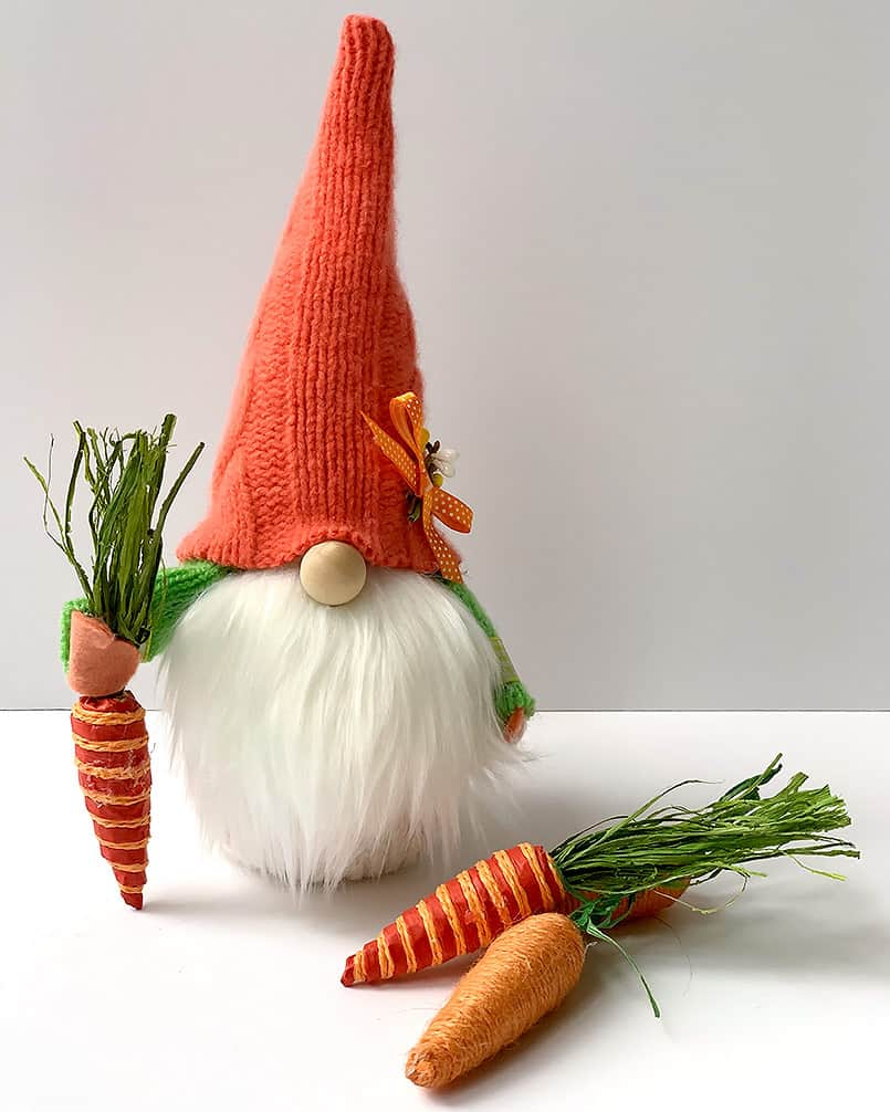 A handmade diy spring gnome holding a carrot, a free tutorial included