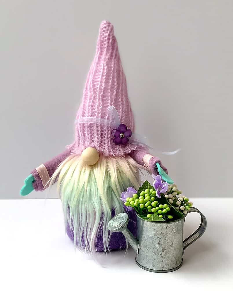 A handmade diy spring gnome holding a watering can filled with flowers, a free tutorial included