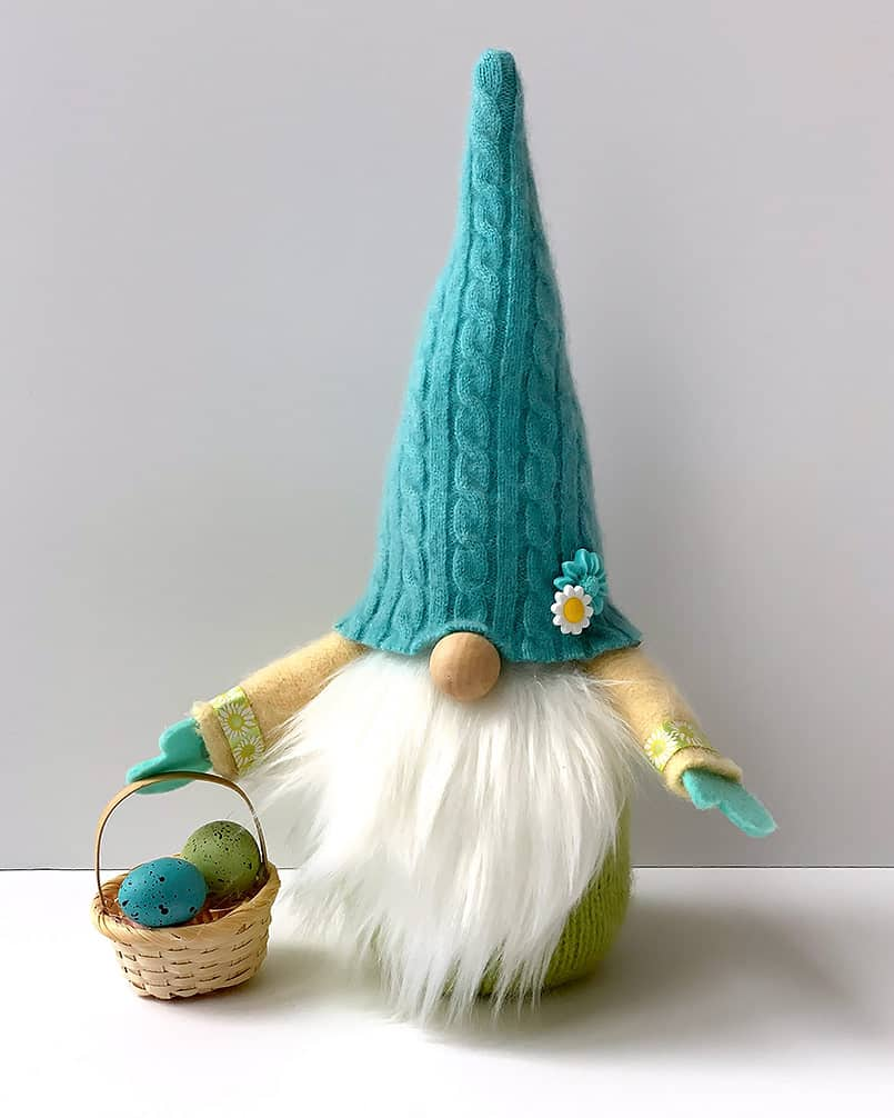 A handmade diy spring gnome holding a easter basket, a free tutorial included