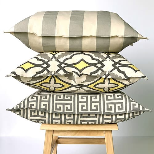 Stack of DIY envelope pillows with flange borders on a bench