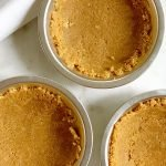 a homemade graham cracker pie crust recipe in 3 small pie tins