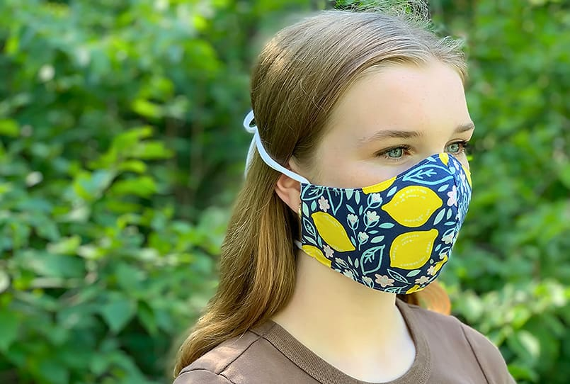 Blue and yellow-flowered DIY fabric face mask worn by a girl with knit ties secured behind her head.