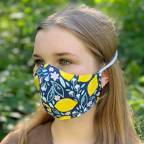 Creative projects with this Blue and yellow-flowered DIY fabric face mask worn by a girl with knit ties secured behind her head.