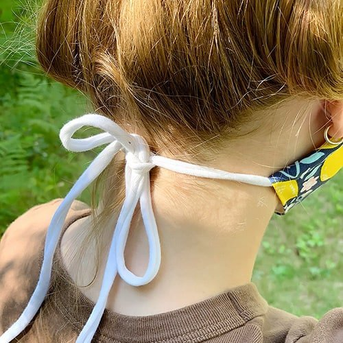 white DIY knit ties being used for a fabric face mask
