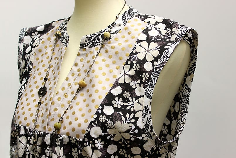 A simple DIY summer dress made with a mix of printed fabric using McCalls M8090 sewing pattern, modeled on a mannequin.