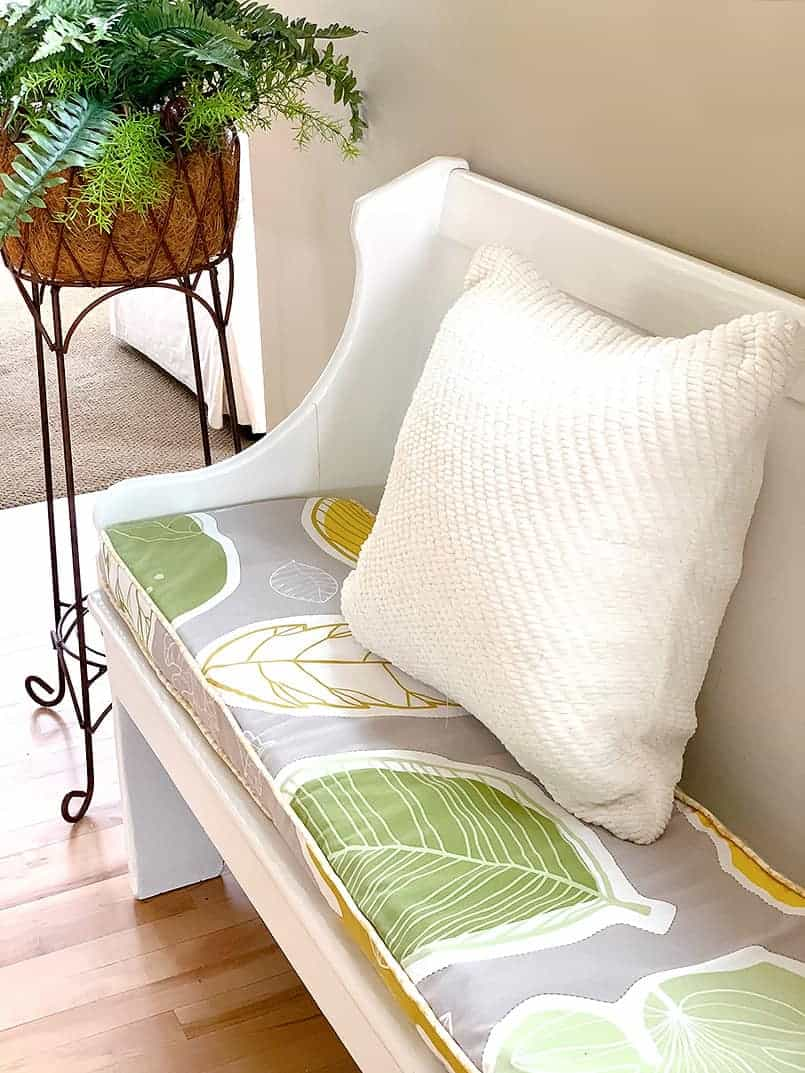 green flower DIY bench seat cushion with cream pillow on a bench.