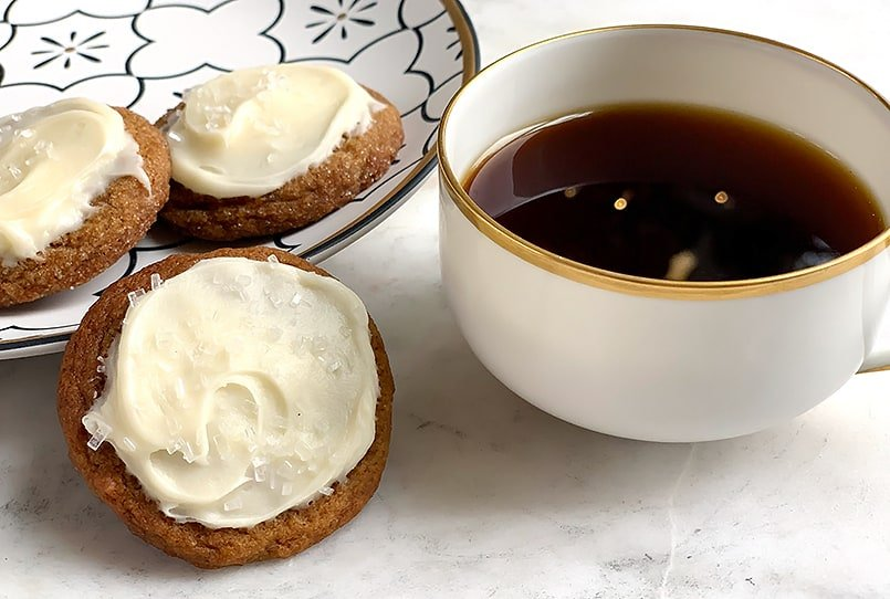 soft ginger cookies with frosting on a porcelain plate with a cup of coffee