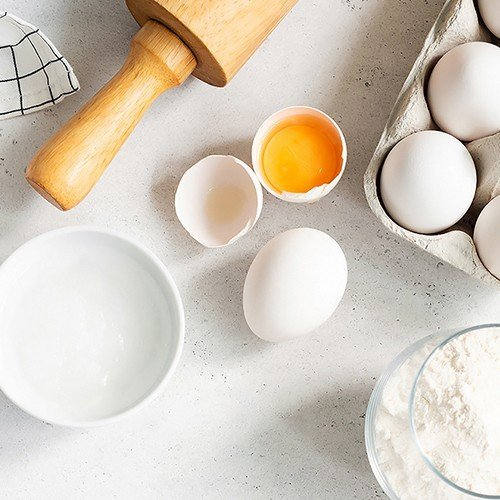 A work area for baking cookies with a rolling pin, flour and eggs