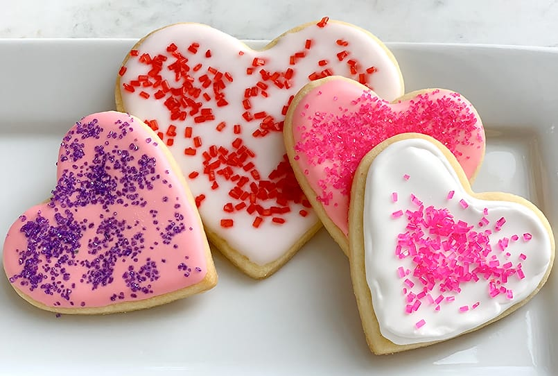 Sprinkles and shades of pink royal icing on the Best Cut Out Sugar Cookies