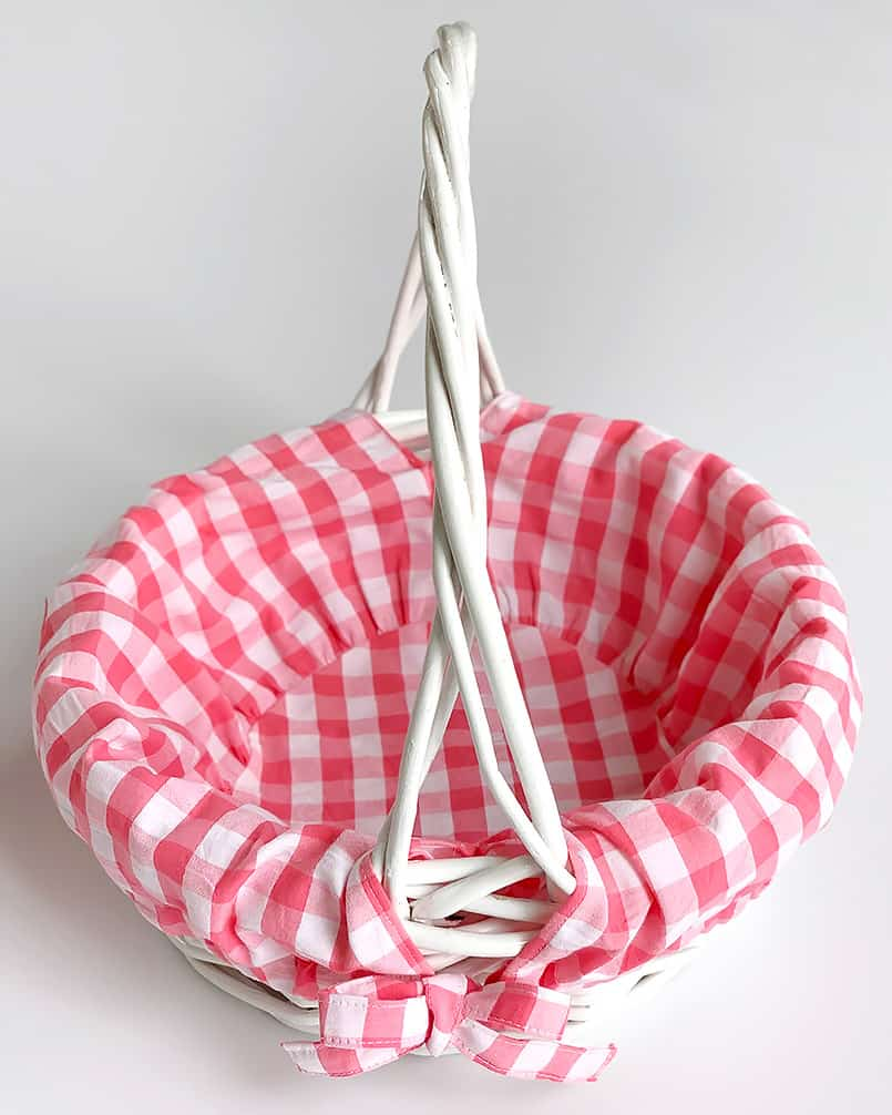 A pink basket liner in a white basket from a blog post on Easter basket ideas.