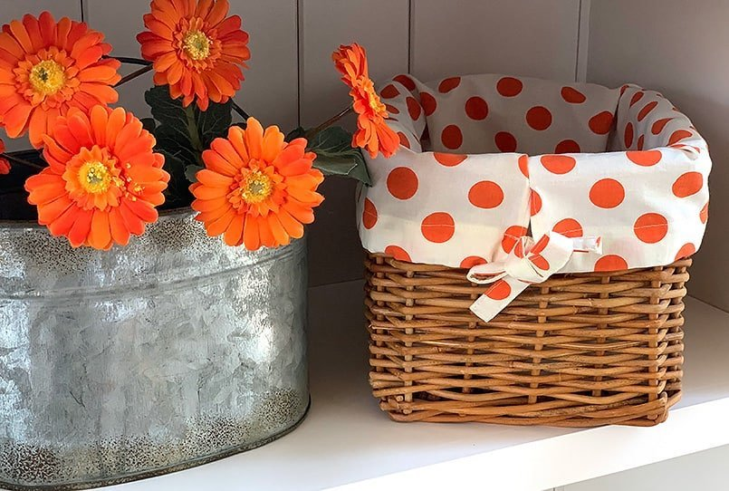 An orange polka dot DIY basket liner on a wicker basket on a white shelf.