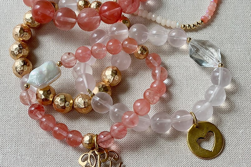5 pink-colored pile of beaded bracelets for a personalized bracelet ideas blog post.