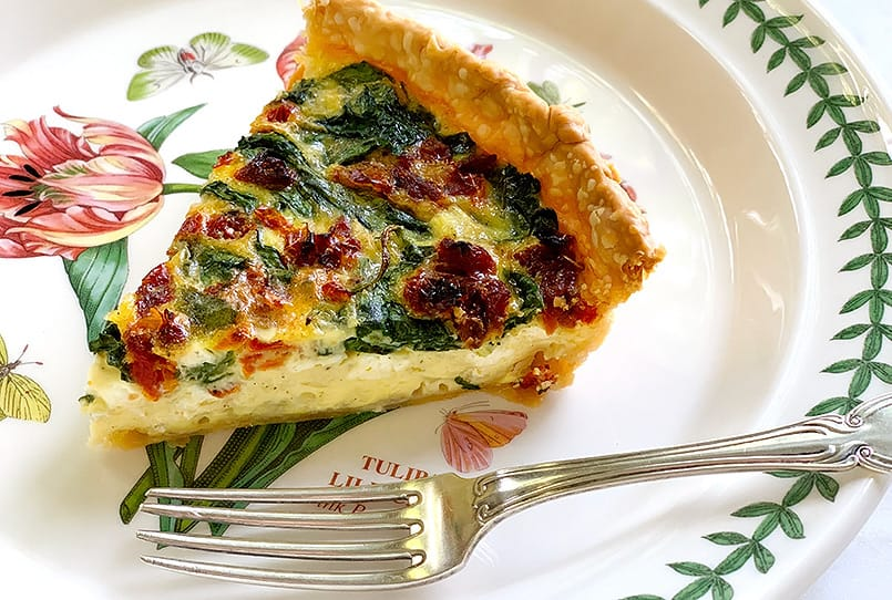 A Spinach Quiche with Sun-Dried Tomatoes and cottage cheese on a plate.