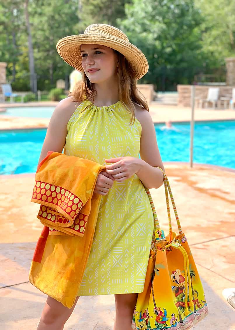 A yellow swim dress modeled at a pool, from the blog post on how to make a halter dress.