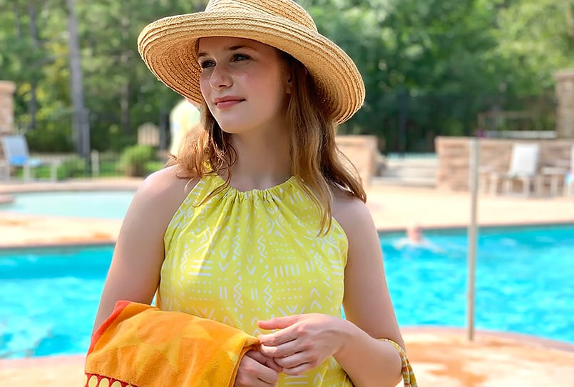 A yellow halter swim dress modeled at a pool, from the blog post on how to make a halter dress.