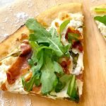 Rosemary and Prosciutto pizza slices on a wood pizza peel.