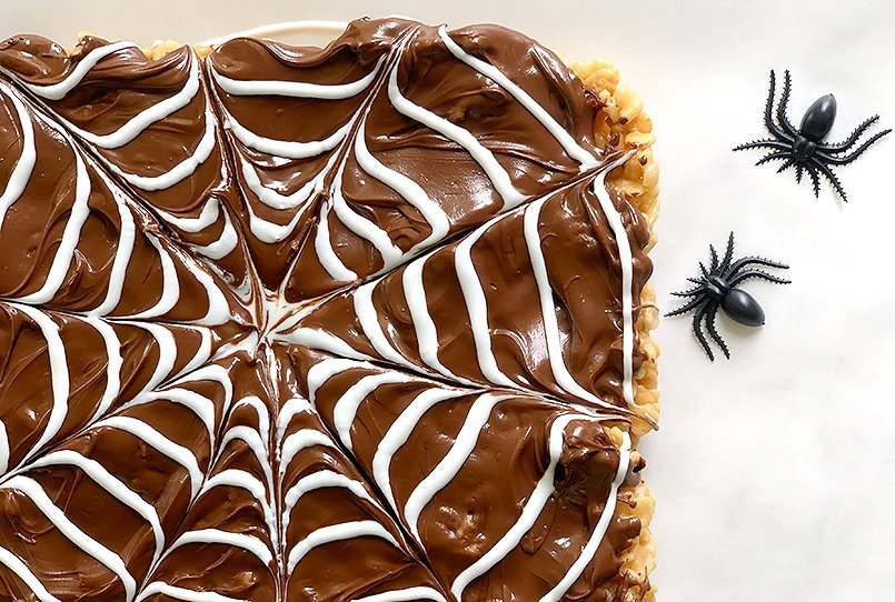 A large piece of Halloween Rice Krispie Treats with 2 fake spiders.