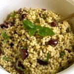 A Pesto Couscous Salad Recipe in a white bowl with a serving spoon.